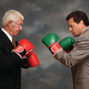 Two businessmen in business suites facing off with boxing gloves